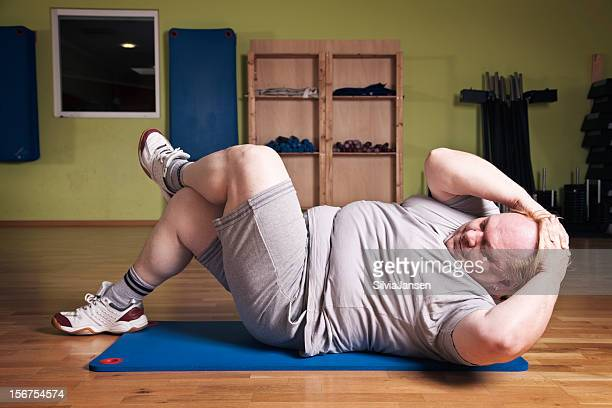 overweight man in gym doing sit-ups