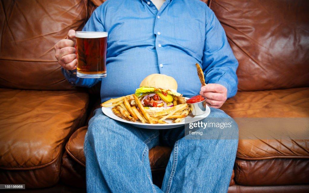 bergewichtige mann ber essen auf einer couch stock foto getty images. Black Bedroom Furniture Sets. Home Design Ideas