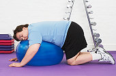 Overweight Man Resting on Exercise Ball