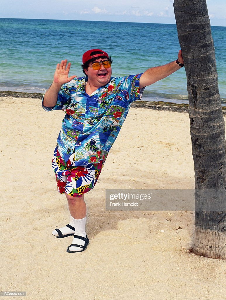 Overweight man standing on beach, leaning on palm tree, waving