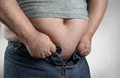 Obesity concept, close up of overweight man trying to wear too small jeans with copy space