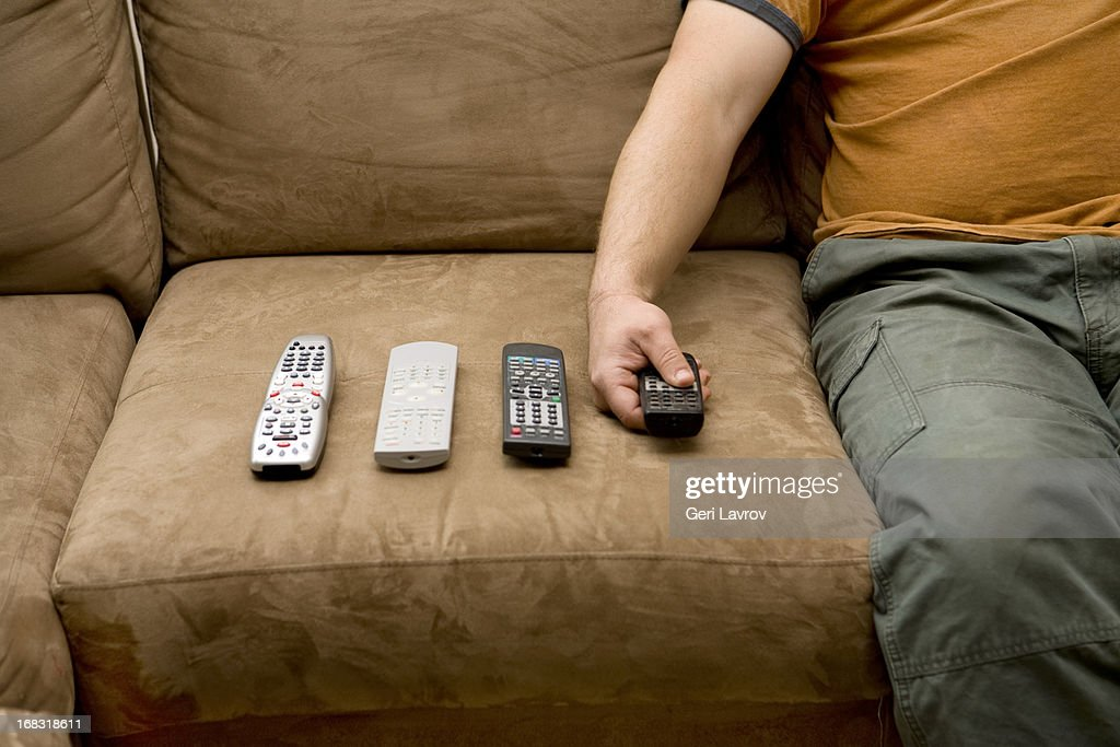 Overweight man using remote controls