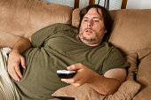 Overweight guy sitting on the couch with remote in hand trying to watch some TV.