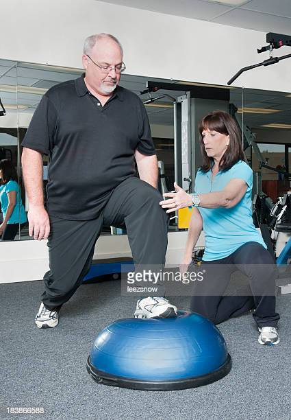 Overweight Man Working Out With Personal Trainer