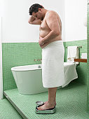 Overweight Man Wrapped in a Towel Stands on a Pair of Scales in a Bathroom