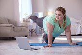 Video lesson. overweight young woman repeating exercises while watching online workout session