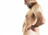 An overweight senior adult man with backache pain is stretching and twisting his torso as he massages his back near his waist with his left hand to try to alleviate the pain. He works out regularly at
