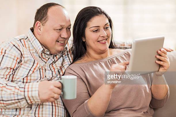 Overweight smiling couple using touchpad at home.