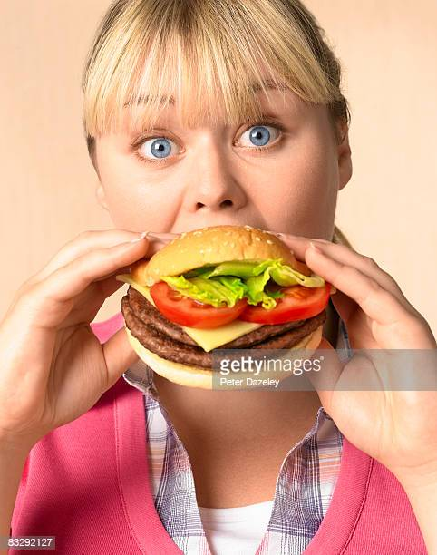Overweight teenager eating burger
