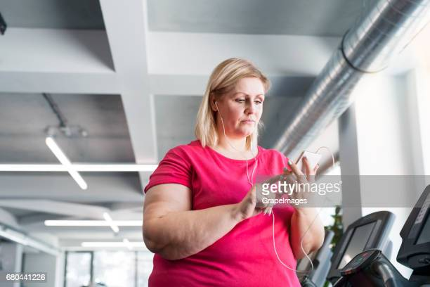 Overweight woman in modern gym at treadmills holding smartphone, listening music.