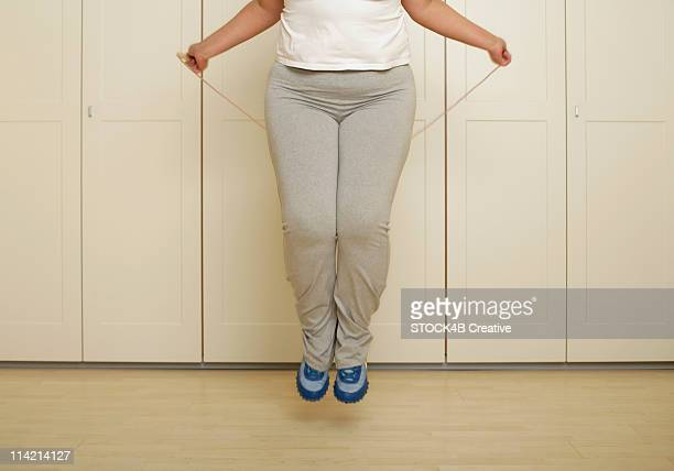 Overweight woman is jumping rope in gym trousers (part of)