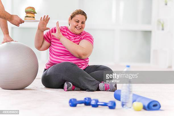 Overweight woman refusing hamburger.