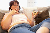 Overweight Woman Relaxing On Sofa Having A Drink And Smoking
