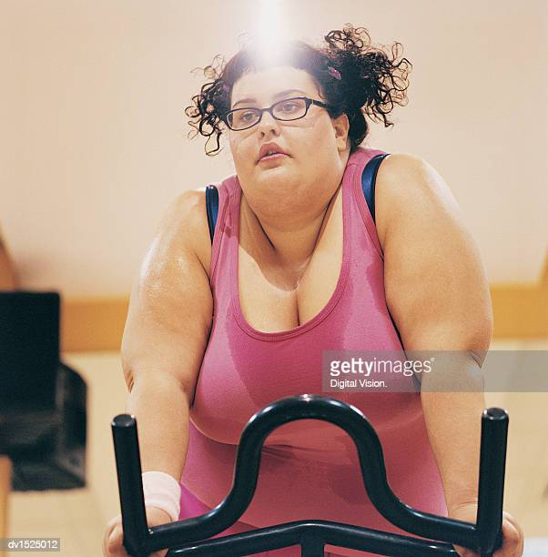 Overweight Woman Riding an Exercise Bike in a Gym