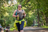 Overweight woman running in the park with a bottle of water listening to music. Weight loss concept.