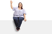Overweight woman sitting on a panel and waving at the camera isolated on white background