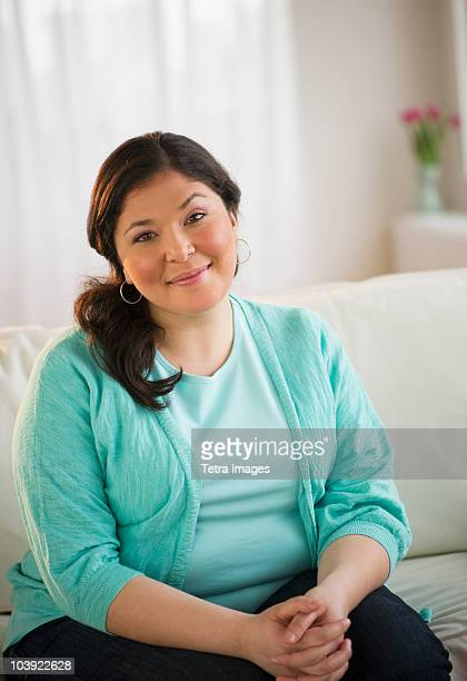 Overweight woman sitting on couch