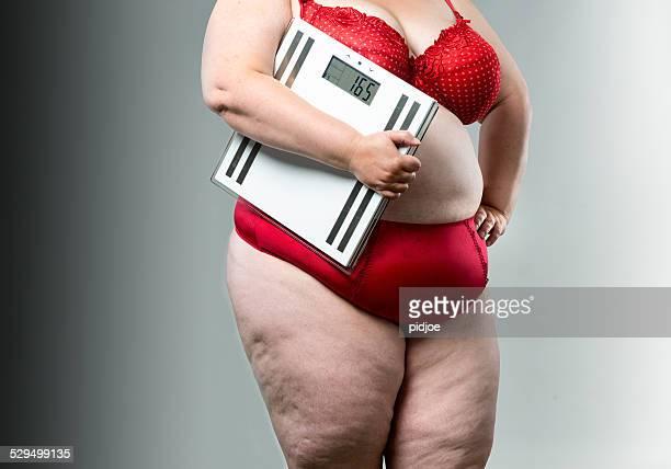 Mulher com excesso de peso com escalas