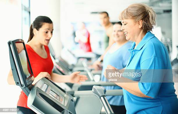 Overweight women exercising on a treadmill.