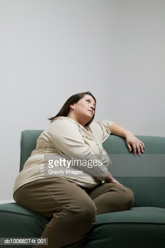 Overweight women sitting on sofa, side view : Stock Photo