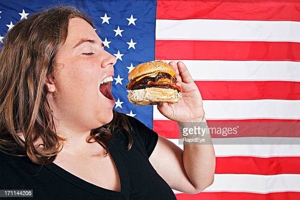 Overweight young woman against American flag prepares to bite cheeseburger