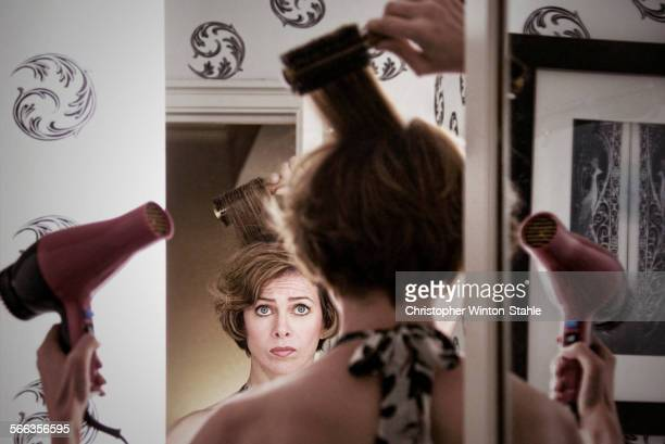 Overwhelmed Caucasian woman styling her hair