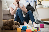 Overwhelmed exhausted woman feeling tired of cleaning in her messy house sitting on the floor with toys and laundry lying around her