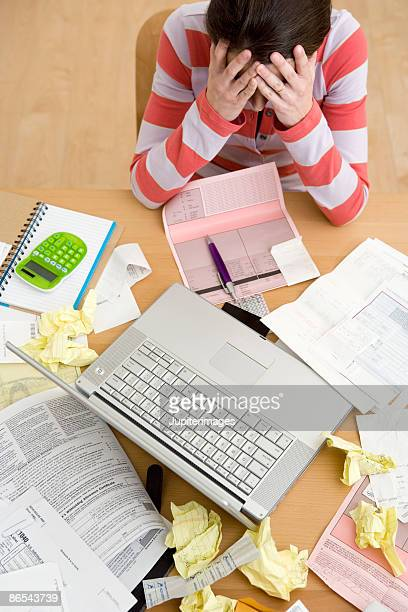 Overwhelmed woman with paperwork and laptop