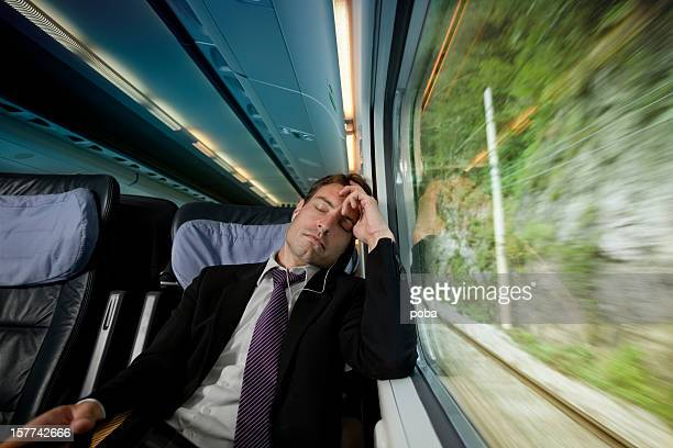overworked  businessman sleeping and listening  music beside  window on train