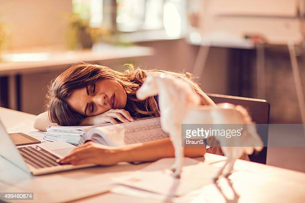 Overworked businesswoman taking a nap on a bunch of paperwork.