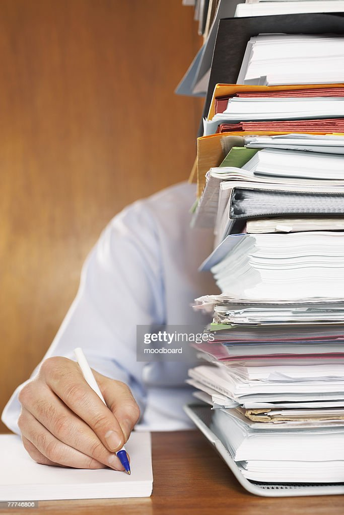 Overworked Man Writing Behind Stack of Files : Stock Photo