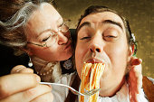 Overzealous Mother Feeding Adult Son Pasta