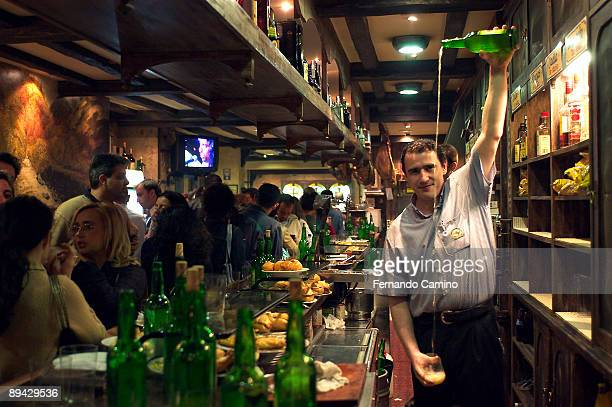 Oviedo Asturias Spain A barman pouring out a glass of cider