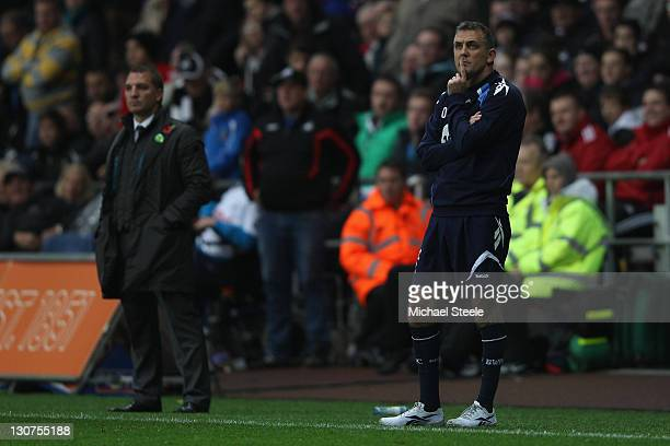Owen Coyle the manager of Bolton looks on pensively alongside Brendan Rodgers manager of Swansea during the Barclays Premier League match between...
