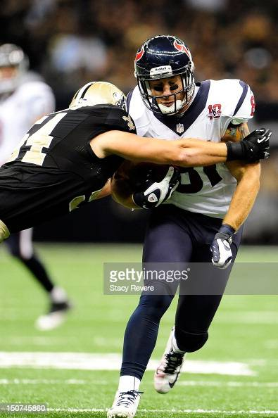 Owen Daniels of the Houston Texans braces for a tackle by Will Herron of the New Orleans Saints during a preseason game at the MercedesBenz Superdome...
