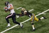 Owen Daniels of the Houston Texans slips a tackle to score a touchdown around Roman Harper of the New Orleans Saints at Louisiana Superdome on...