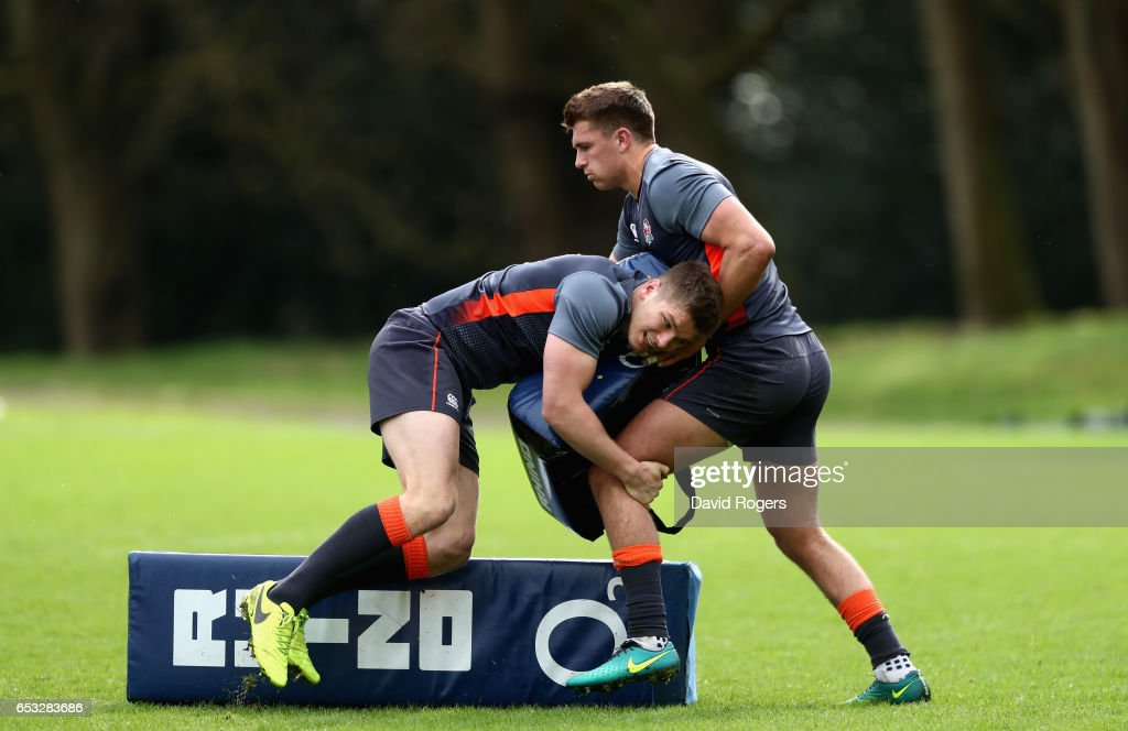 Owen Farrell hits a tackle bag held by Henry Slade during the England training session held at Pennyhill Park on March 14, 2017 in Bagshot, England.