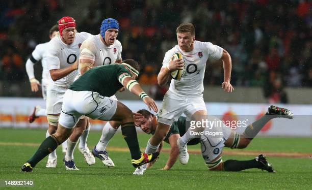 Owen Farrell of England is tackled by Werner Kruger during the third test match between the South Africa Springboks and England at the Nelson Mandela...
