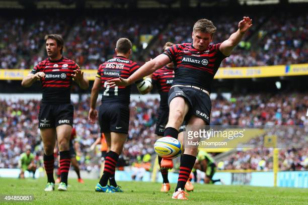 Owen Farrell of Saracens injures himself as he kicks the ball in celebration of a try that was later disallowed during the Aviva Premiership Final...