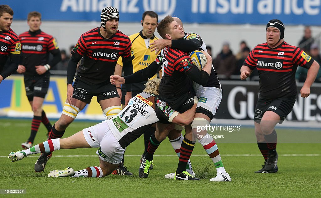 <a gi-track='captionPersonalityLinkClicked' href=/galleries/search?phrase=Owen+Farrell&family=editorial&specificpeople=4809668 ng-click='$event.stopPropagation()'>Owen Farrell</a> of Saracens is tackled by Matt Hopper (L) and George Robson during the Aviva Premiership match between Saracens and Harlequins at Allianz Park on March 24, 2013 in Barnet, England.