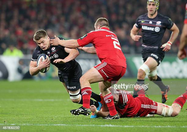 Owen Farrell of Saracens is tackled during the European Rugby Champions Cup match between Munster and Saracens at Thomond Park on October 24 2014 in...