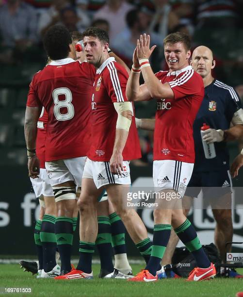 Owen Farrell of the Lions applauds the referee Steve Walsh after showing the yellow card to Barbarian hooker Schalk Brits during the match between...