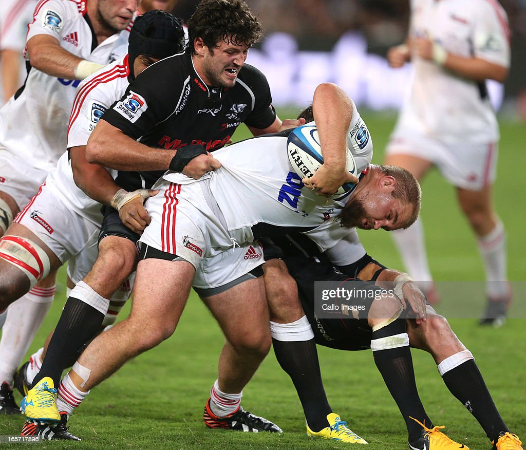 Owen Franks of Crusaders is tackled by Ryan Kankowski and Keegan Daniel of Sharks during the Super Rugby round eight match between the Sharks and Crusaders from Kings Park on April 05, 2013 in Durban, South Africa.