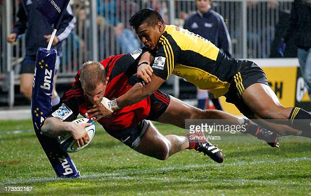 Owen Franks of The Cruaders is tackled by Julian Savea of the Hurricanes during the round 20 Super Rugby match between the Crusaders and the...