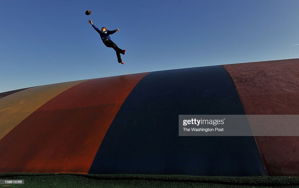 Owen Marino, 12, of Arlington, VA stretches out to catch a football as he plays on 'The Jumping Pillow' at Ticonderoga Farms on Sunday November 25, 2012 in Chantilly, VA. The farm has over 4,000 trees that can be picked out and cut.