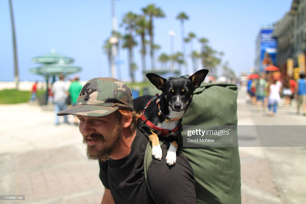 Owen McHugh, who has been living on the streets for nine years, walks the Venice Beach Boardwalk with his dog Baby Girl on Independence Day weekend at Venice Beach on July 6, 2013 in Venice, California. An estimated 16 million people visit the famous beach city annually which is celebrating 108th birthday as of July 4.
