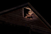 Owl taking off from barn window at night