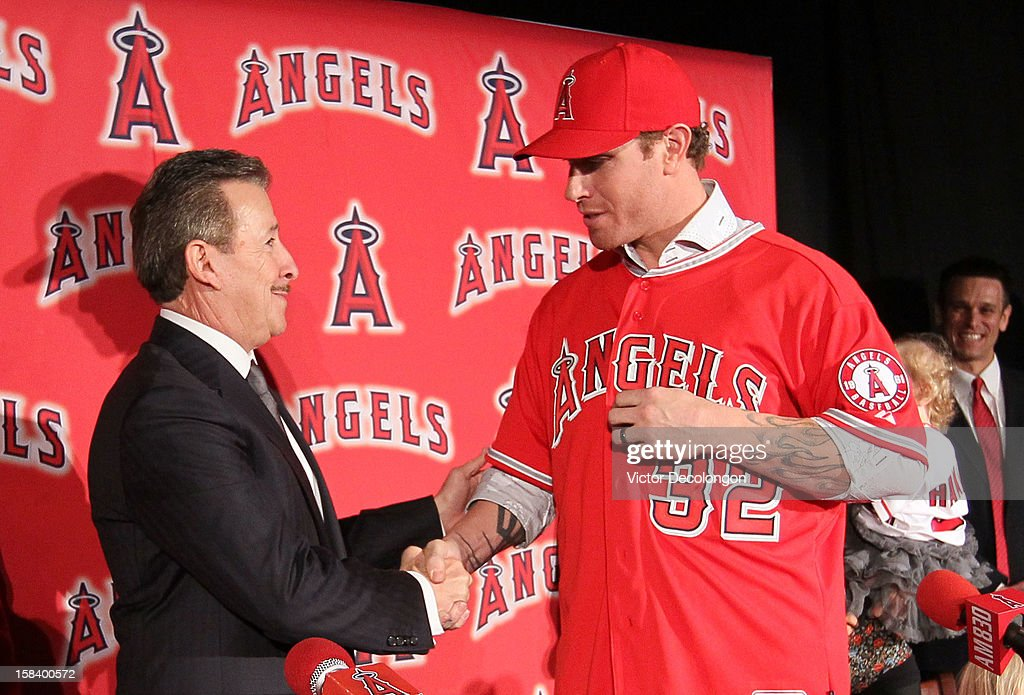 Owner Arte Moreno of the Los Angeles Angels of Anaheim and Josh Hamilton #32 of the Los Angeles Angels of Anaheim shake hands as Angels General Manager Jerry Dipoto (R) smiles in the background during the press conference to introduce Hamilton as the team's newest member at ESPN Zone at Downtown Disney on December 15, 2012 in Anaheim, California.
