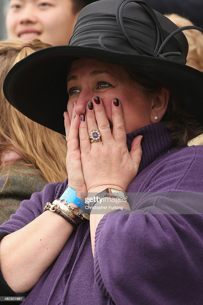 Owner Belinda Sparey nervously watches her horse Swallows Delight take part in the the Crabbie's Supporting The Hillsborough Families Fox Hunters' Steeple Chase at Aintree Racecourse on April 3, 2014 in Aintree, England. The three days of racing attracts thousands of racegoers and fans from across the world. The meeting culminates with millions of pounds being wagered on the runners taking part in Europe's richest jump race, the Grand National.