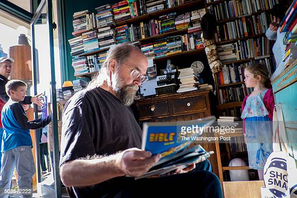 Owner Bud Burwell looks over a group incoming used books from a customer at the Reston Used Book Shop on Sunday November 22 2015 in Reston Virginia...